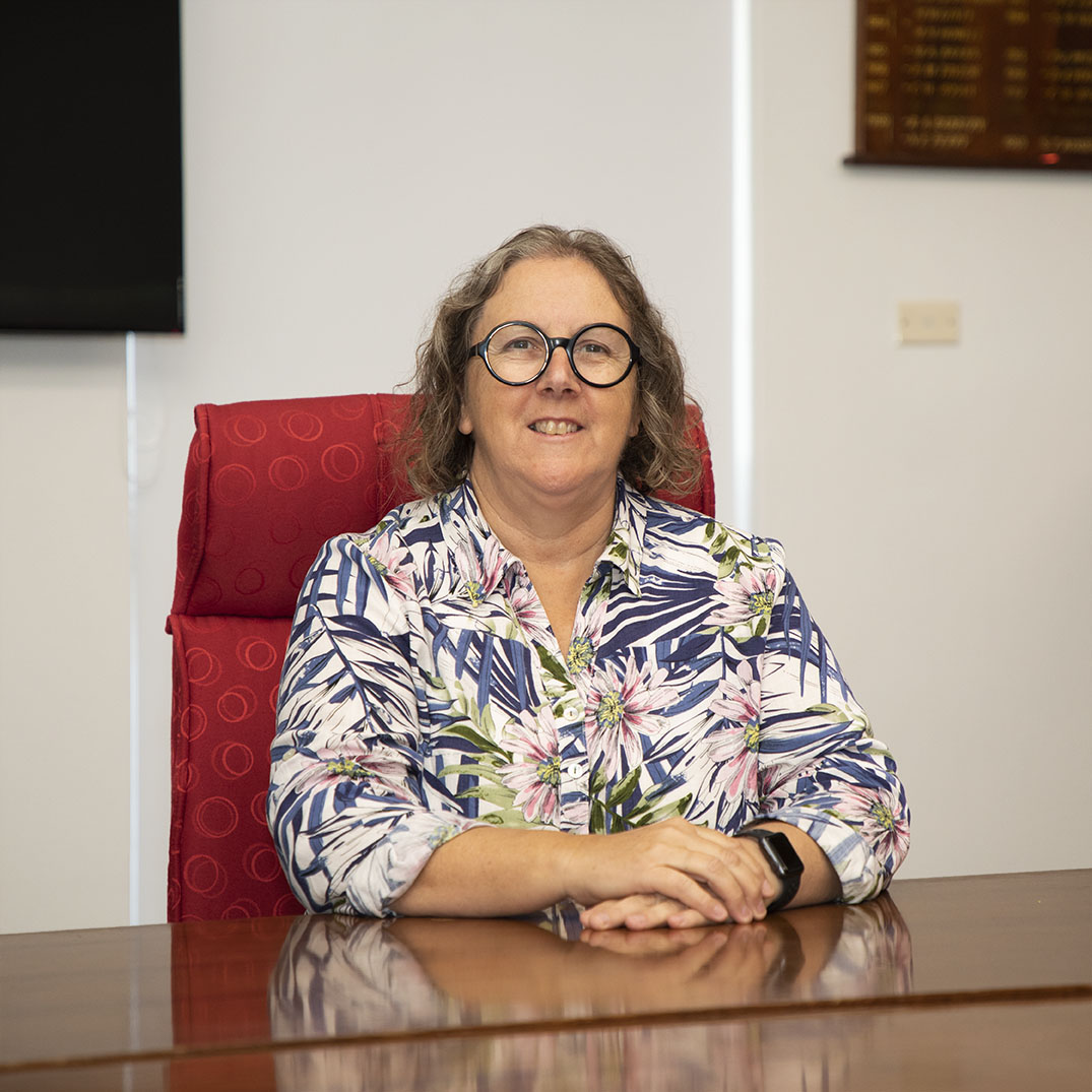 Female General Manager, sitting at board room table, smiling