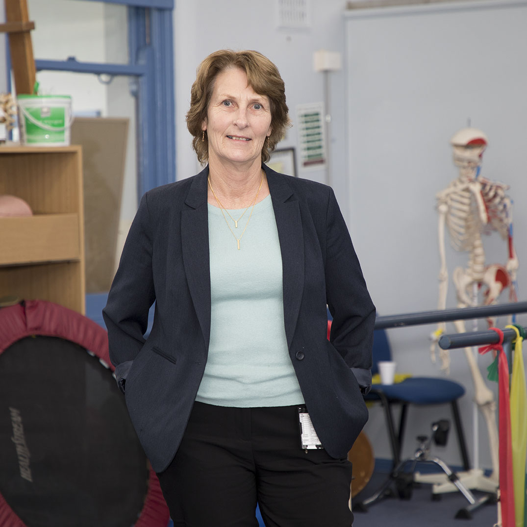 Female, Manager of Allied Health Services standing with hands in pockets in a physiotherapy room, smiling
