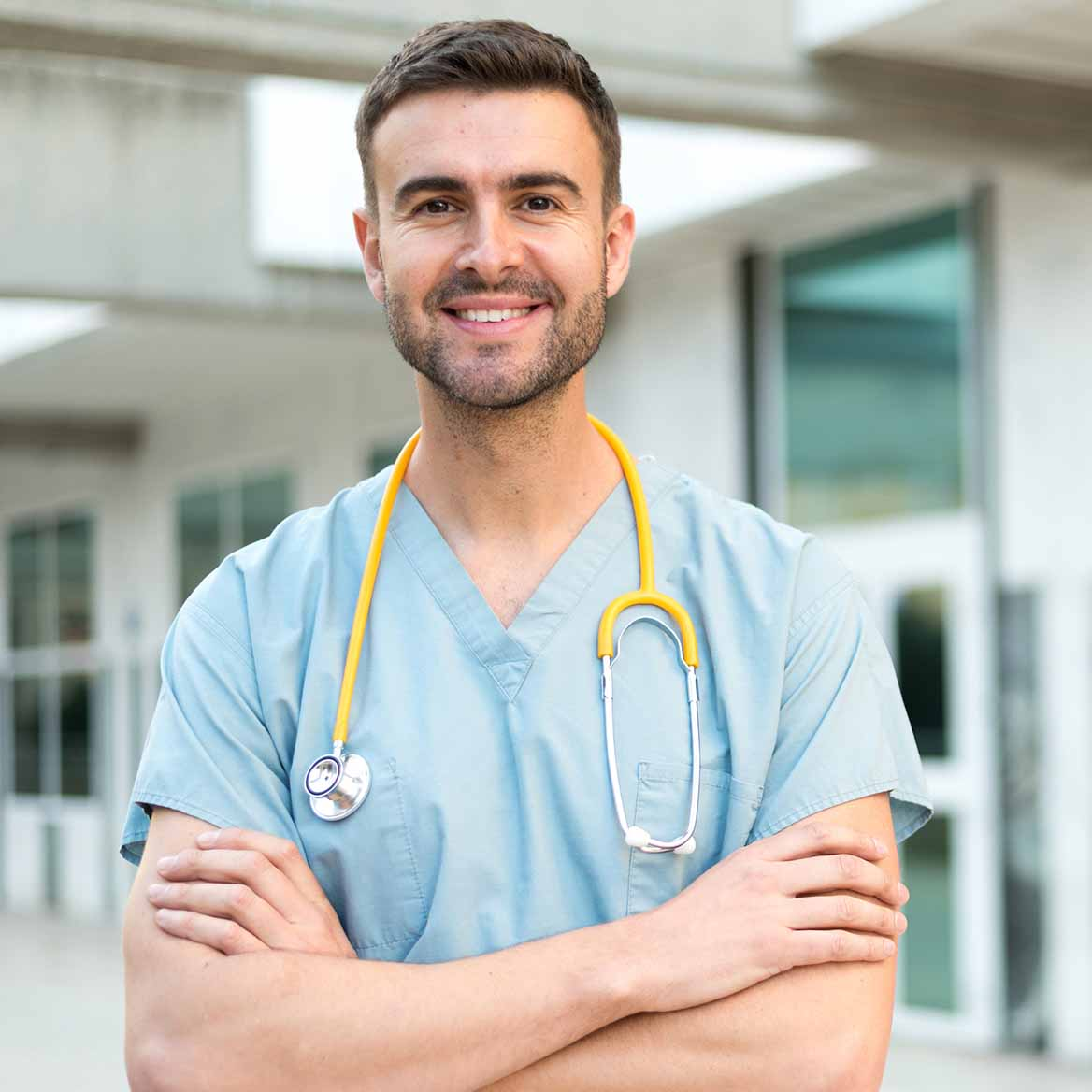 Image of male doctor with stethoscope around neck, in scrubs and smiling
