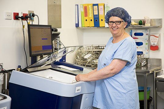 Clinical Sterilisation Department worker in scrubs using sterilising unit and smiling