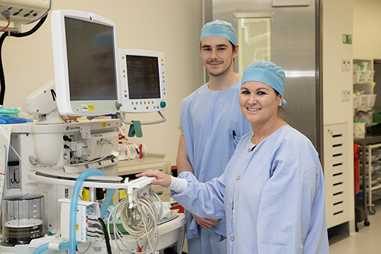 Male nurse and female nurse in scrubs next to monitors and smiling