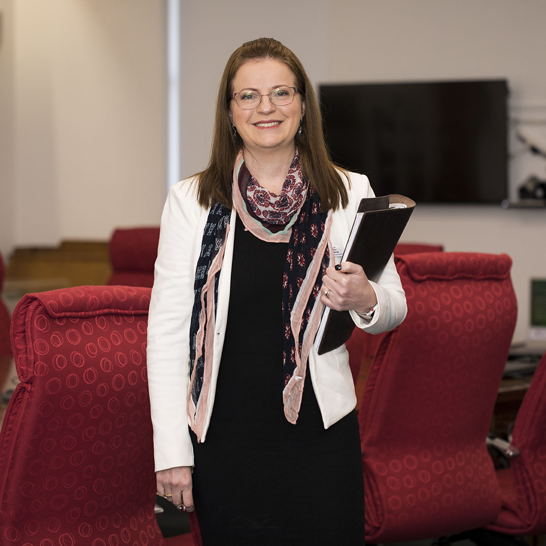 Female, Business Manager standing in board room, holding a folder and smiling